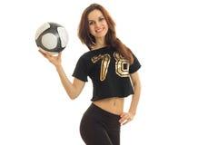 Muchacha hermosa que sonríe en un traje de los deportes, sosteniendo en su mano la bola Foto de archivo libre de regalías