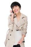 Muchacha hermosa que sonríe mientras que usa el teléfono móvil Fotografía de archivo libre de regalías