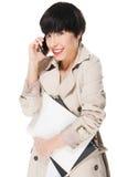 Muchacha hermosa que sonríe mientras que usa el teléfono móvil Fotos de archivo libres de regalías