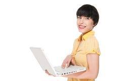 Muchacha hermosa que sonríe mientras que usa el ordenador portátil Foto de archivo libre de regalías