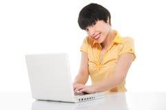 Muchacha hermosa que sonríe mientras que usa el ordenador portátil Imagenes de archivo