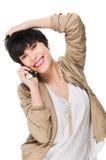 Muchacha hermosa que sonríe mientras que usa el teléfono celular Fotografía de archivo libre de regalías