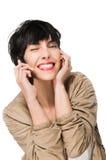 Muchacha hermosa que sonríe mientras que usa el teléfono celular Fotos de archivo libres de regalías