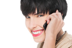 Muchacha hermosa que sonríe mientras que usa el teléfono celular Fotografía de archivo