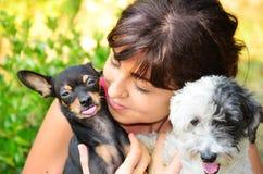 Muchacha hermosa que sonríe y que abraza dos pequeños perros Fotos de archivo libres de regalías