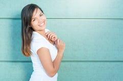 Muchacha hermosa que sonríe y que presenta la camiseta blanca que lleva Fotos de archivo