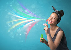 Muchacha hermosa que sopla burbujas y líneas coloridas abstractas Imagen de archivo