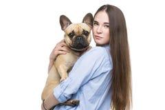 Muchacha hermosa que sostiene el dogo francés Fotografía de archivo libre de regalías