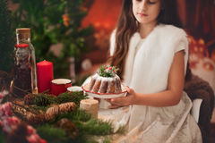 Muchacha hermosa que sostiene en sus manos una torta de la Navidad Imagen de archivo libre de regalías