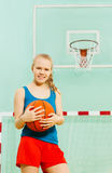 Muchacha hermosa que sostiene la bola debajo de aro de baloncesto Foto de archivo libre de regalías