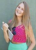 Muchacha hermosa que sostiene la tableta disponible Imágenes de archivo libres de regalías
