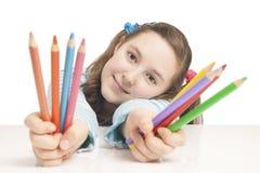 Muchacha hermosa que sostiene los lápices del color Imagenes de archivo