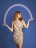 Muchacha hermosa que sostiene un arco iris en un backgro azul Imagen de archivo