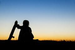 Muchacha hermosa que sostiene un monopatín con la puesta del sol en el backg Foto de archivo