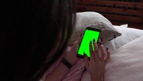 Muchacha hermosa que sostiene un smartphone en las manos de una pantalla verde del verde de la pantalla metrajes