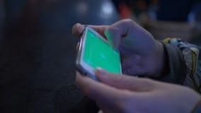 Muchacha hermosa que sostiene un smartphone en las manos de una pantalla verde del verde de la pantalla, mano del hombre que sost metrajes