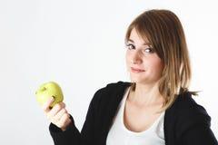 Muchacha hermosa que sostiene una manzana en sus manos, en un backgro blanco imagenes de archivo