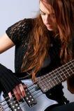 Muchacha hermosa que toca la guitarra baja Imagen de archivo libre de regalías