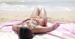 Muchacha hermosa que toma el sol en la playa metrajes