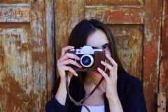 Muchacha hermosa que toma la imagen con la cámara vieja Fotografía de archivo