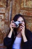 Muchacha hermosa que toma la imagen con la cámara vieja Fotos de archivo libres de regalías