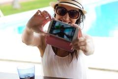 Muchacha hermosa que toma un selfie en la piscina Foto de archivo