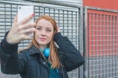 Muchacha hermosa que toma un selfie en las calles de la ciudad Imágenes de archivo libres de regalías