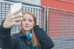 Muchacha hermosa que toma un selfie en las calles de la ciudad Foto de archivo