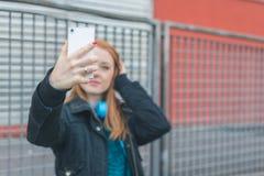 Muchacha hermosa que toma un selfie en las calles de la ciudad Imagenes de archivo