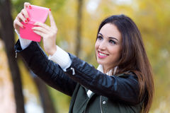 Muchacha hermosa que toma un selfie en otoño Foto de archivo libre de regalías
