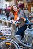Muchacha hermosa que toma una bici para el alquiler en París imagen de archivo