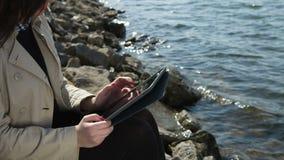 Muchacha hermosa que trabaja en la tableta en la playa almacen de video