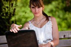 Muchacha hermosa que usa la computadora portátil Imágenes de archivo libres de regalías