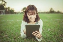 Muchacha hermosa que usa la tableta en parque verde Fotos de archivo