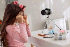 Muchacha hermosa que usa los rodillos del pelo y registrando el tutorial video Fotografía de archivo libre de regalías