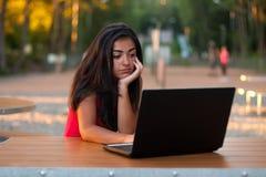 Muchacha hermosa que usa su computadora portátil - pensando Foto de archivo libre de regalías