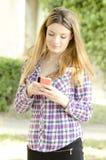 Muchacha hermosa que usa un smartphone Fotos de archivo libres de regalías