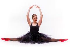 Muchacha hermosa rubia en el vestido negro del tutú que hace fractura gimnástica Foto de archivo