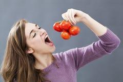 Muchacha hermosa 20s que come los tomates con el apetito para las vitaminas y la comida apetitosa Imagen de archivo