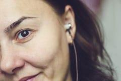 Muchacha hermosa, señora joven con los auriculares en sus oídos imagen de archivo