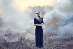 Muchacha hermosa sensual en humo en natur foto de archivo