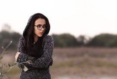 Muchacha hermosa sola sola en suéter caliente con la capilla que mira a un lado en fondo del campo del otoño Imagen de la O.N.U t imagenes de archivo