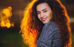 Muchacha hermosa sonriente con rizado, pelo iluminado por el sol Fotografía de archivo libre de regalías