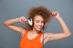 Muchacha hermosa sonriente del positivo que escucha la música y el baile Fotografía de archivo