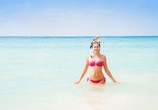 Muchacha hermosa, sonriente en el salto rosado del bikini en el mar Fotografía de archivo