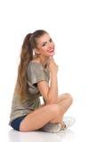 Muchacha hermosa sonriente que se sienta con las piernas cruzadas Imagen de archivo