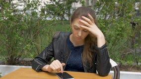 Muchacha hermosa triste que se sienta en una tabla en un café Lee SMS en un smartphone Tristeza y anhelo, desesperación Primer almacen de metraje de vídeo