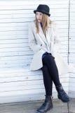 Muchacha hermosa triste sola en una capa y un sombrero negros, sentándose en un día soleado frío del invierno del banco blanco Foto de archivo libre de regalías
