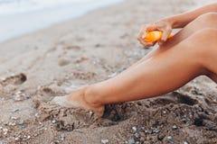 Muchacha hermosa, uso poner crema del sol, en la playa, pies de primer, tarro de crema del sol, aislado imagenes de archivo