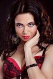 Muchacha hermosa y atractiva que lleva la ropa interior roja sobre oscuridad.   Imagen de archivo libre de regalías
